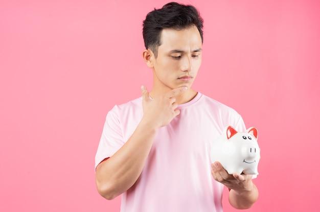 Hombre asiático joven que sostiene la hucha en rosa
