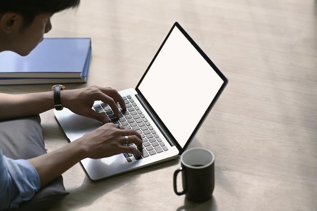 Hombre asiático joven que trabaja con la computadora portátil mientras está acostado en el piso de madera en la sala de estar en casa.