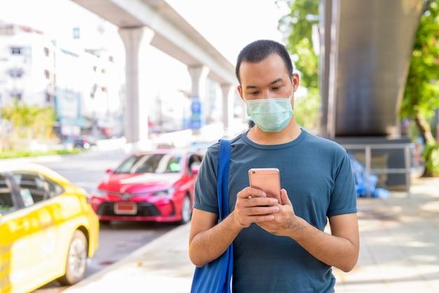 Hombre asiático joven que usa el teléfono con máscara para protegerse del brote de coronavirus en la estación de taxis de la ciudad