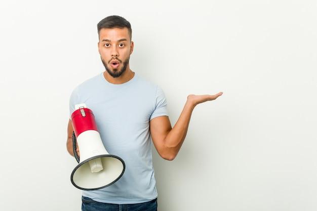 Hombre asiático joven de raza mixta sosteniendo un megáfono impresionado sosteniendo espacio de copia en la palma.