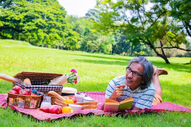 El hombre asiático joven relaja tiempo en parque por la mañana está leyendo un libro.