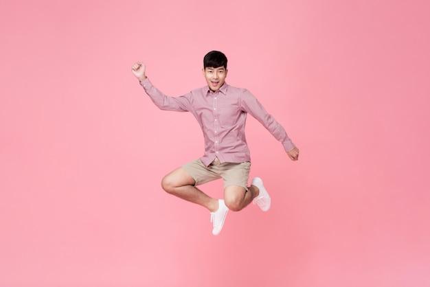 Hombre asiático joven sonriente enérgico en el salto casual de la ropa