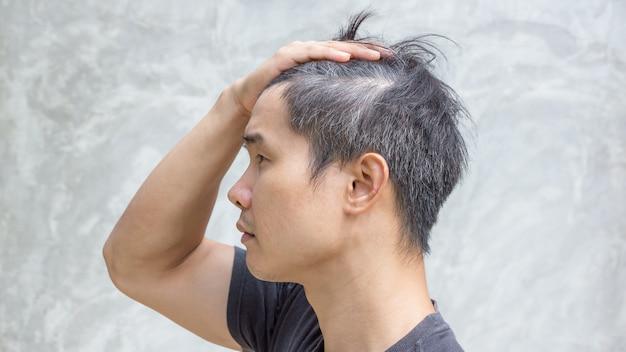 El hombre asiático joven tiene un pelo gris.