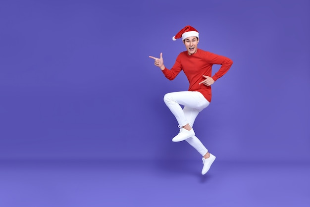 Hombre asiático joven en traje casual rojo con sombrero de santa saltando con el dedo acusador a un lado frente a un espacio de copia y cara de sonrisa en la pared púrpura. concepto de feliz año nuevo.