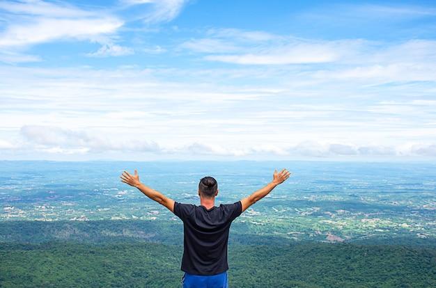 El hombre asiático levanta sus brazos en el punto de vista de las montañas en el botón de piedra del patio en el parque nacional de phu hin rong kla, phitsanulok, tailandia.