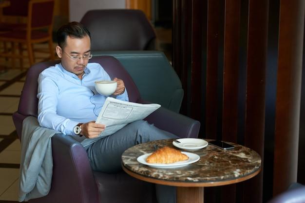 Hombre asiático leyendo mañana tabloide piernas cruzadas en la cafetería