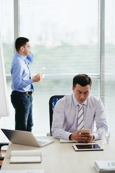 Hombre asiático leyendo mensajes de texto con su colega haciendo una llamada telefónica en el fondo