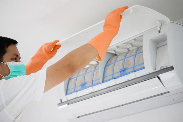 Hombre asiático limpieza filtro sucio del aire acondicionado