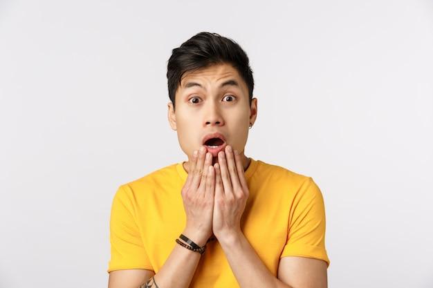 Hombre asiático lindo en camiseta amarilla con la boca abierta