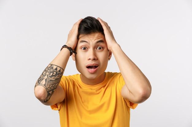 Hombre asiático lindo en camiseta amarilla tomados de la mano en la cabeza