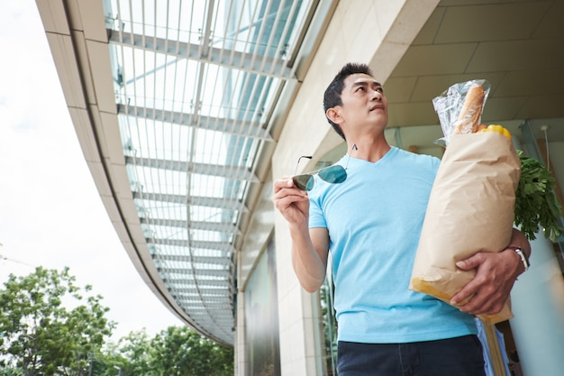 Hombre asiático llevando bolsa con comestibles a través del centro comercial y mirando a su alrededor