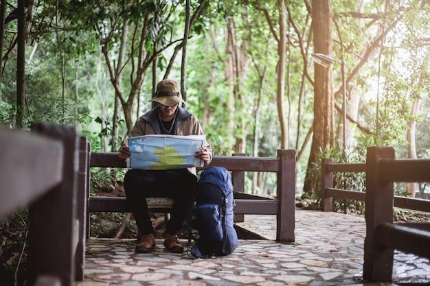 Hombre asiático con mapa y sombrero sentado y viendo el mapa
