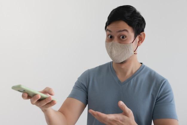 Hombre asiático con máscara está contento con la promoción en la aplicación para teléfonos inteligentes.