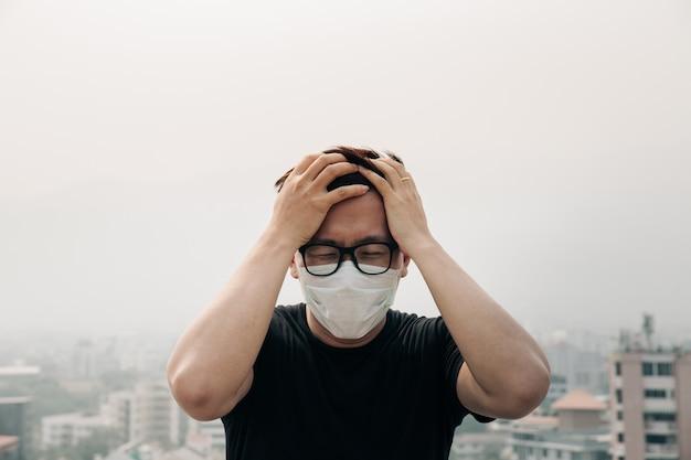 Hombre asiático con máscara de higiene y enfermo debido a la contaminación del aire en la ciudad.