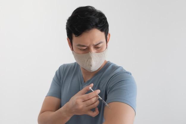 Hombre asiático con mascarilla está inyectando una vacuna. concepto de protección antivirus.