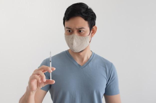 Hombre asiático con una mascarilla está inyectando una vacuna