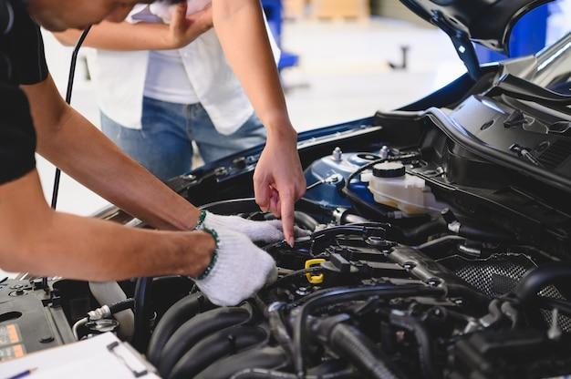 Hombre asiático mecánico de automóviles examinar el problema de avería del motor del automóvil frente a automotriz