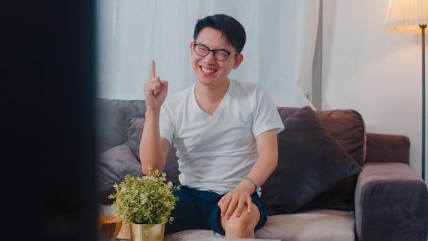 El hombre asiático de mediana edad disfruta del tiempo libre para relajarse en casa. estilo de vida chico feliz diversión ver televisión animando fútbol y ver entretenimiento en la sala de estar en casa moderna en la noche.
