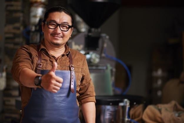 Hombre asiático de mediana edad posando con el pulgar hacia arriba frente al equipo de tostado de café