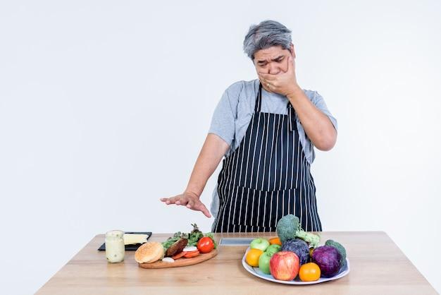 Un hombre asiático de mediana edad usa su mano para cubrirse la boca y rechazar una hamburguesa