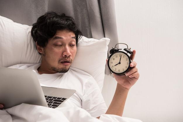 El hombre asiático en la mirada de la cama en el despertador cuando despierta después de consiguió dormir mientras que trabajaba en la computadora.