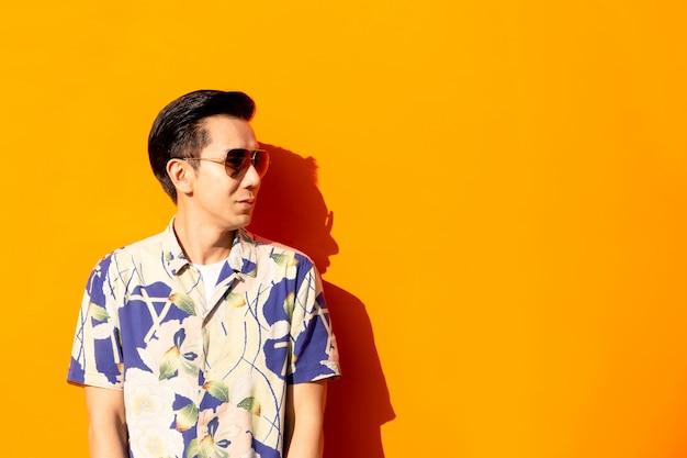 Hombre asiático de la moda con las gafas de sol en fondo coloreado.