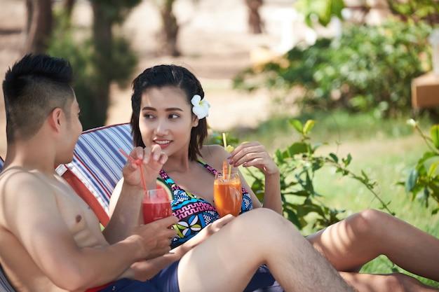 Hombre asiático y mujer bebiendo cócteles en lujoso resort tropical