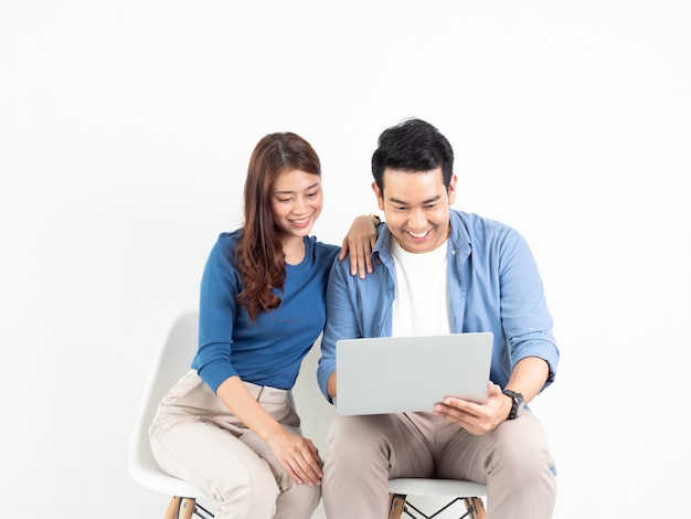 Hombre asiático y mujer que hablan con el ordenador portátil para el negocio en el fondo blanco