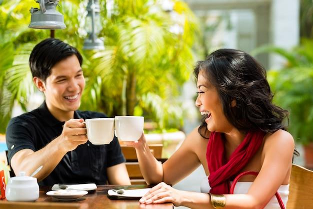 Hombre asiático y mujer en restaurante o cafetería