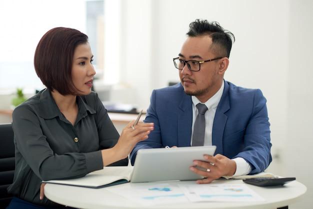 Hombre asiático y mujer en traje de negocios sentado en el interior con tableta y hablando