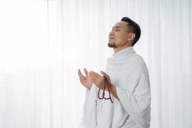 Hombre asiático musulmán rezando con rosarios