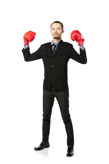Hombre asiático de negocios listo para luchar con guantes de boxeo.
