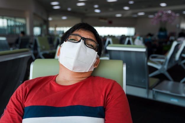 Hombre asiático obeso vestido con mascarilla protectora sentarse durmiendo en el asiento de distanciamiento social en el aeropuerto