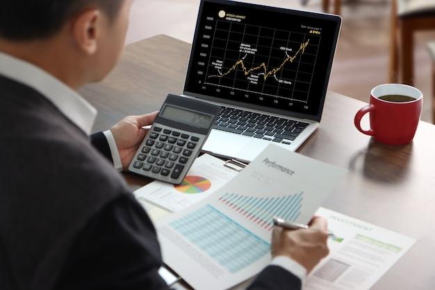 Hombre asiático en la oficina sosteniendo una calculadora frente a la computadora portátil mientras revisa el gráfico del mercado bursátil analizando un riesgo de inversión.