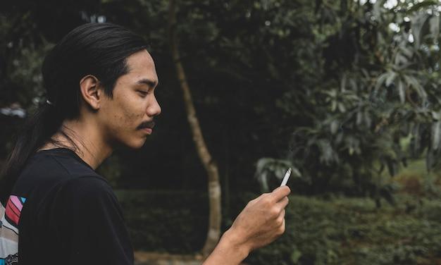 Un hombre asiático de pelo largo con barba sosteniendo un cigarrillo de pie afuera.