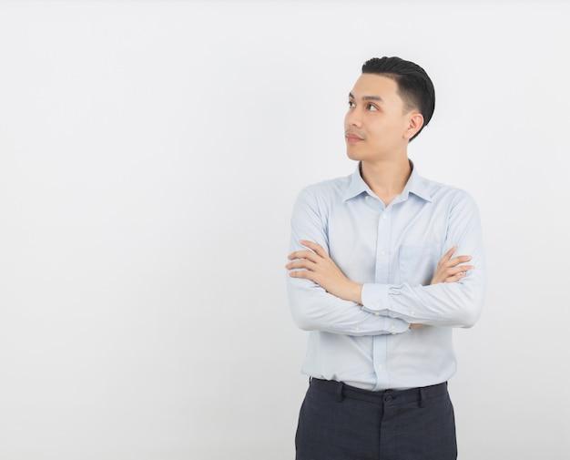 Hombre asiático pensando una idea mientras mira hacia arriba con los brazos cruzados aislado sobre fondo blanco.
