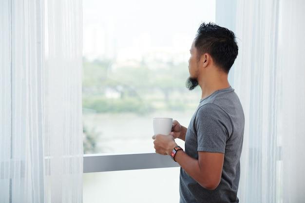 Hombre asiático de pie delante de la ventana alta con taza y mirando