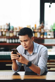 Hombre asiático de pie detrás del mostrador en la barra y con smartphone