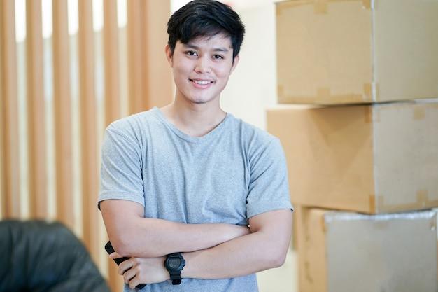 Hombre asiático de pie sobre cajas grandes de cartón después de mudarse a un nuevo hogar