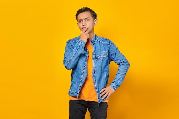 Hombre asiático piensa en algo y toca su barbilla sobre fondo amarillo