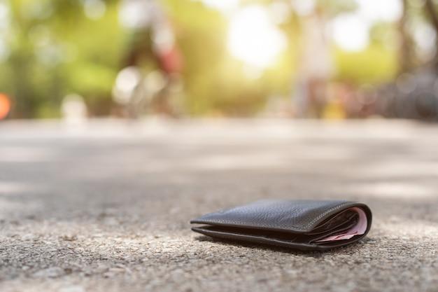 Hombre asiático pierde billetera negra en la carretera en atracción turística