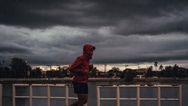 El hombre asiático está practicando correr. el esta bajo la lluvia.