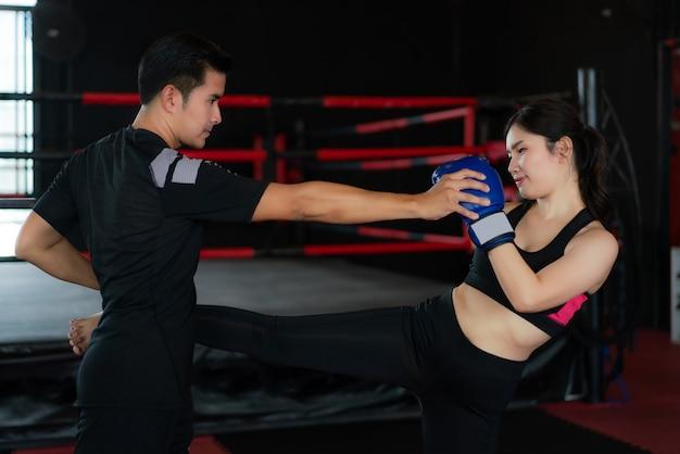Hombre asiático practicante entrenador profesional pateando a joven boxeador en el estadio de boxeo