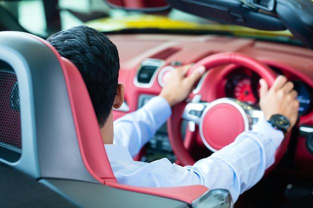Hombre asiático probando un nuevo coche deportivo en un concesionario de coches