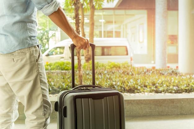 Hombre asiático que se coloca con equipaje de la maleta en el concepto del viaje del terminal de aeropuerto.