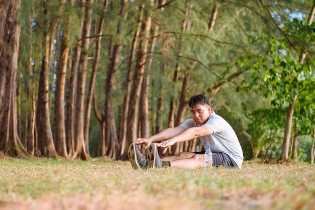 Hombre asiático que estira el cuerpo antes de correr en el parque y el atardecer