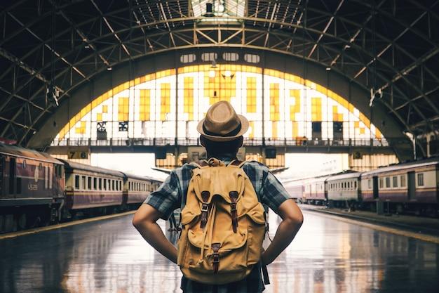 Hombre asiático que hace excursionismo comenzando a viajar en la estación de tren, viaje en concepto de vacaciones.