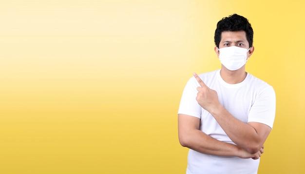 El hombre asiático que lleva una máscara está enfermo señalando con el dedo aislado
