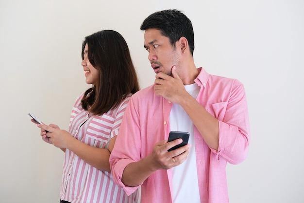 Hombre asiático que mira a escondidas a su esposa teléfono móvil con expresión sospechosa