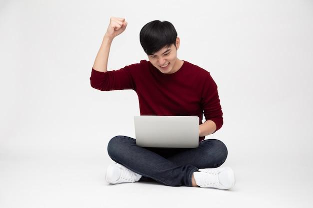 Hombre asiático que se siente feliz sosteniendo la computadora portátil mientras está sentado en un piso aislado en blanco